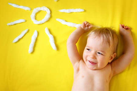 little boy with sunglasses and sun shape on yellow blanket Stock Photo