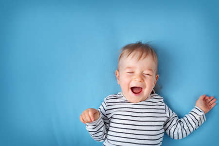 happy little boy on blue blanket background Stock Photo