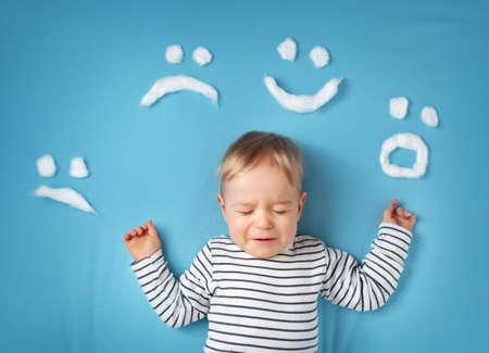 psicologia infantil: feliz niño pequeño en el fondo manta azul con caras sonrientes Foto de archivo