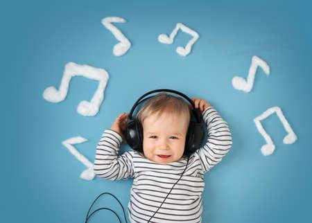 oir: feliz niño pequeño en el fondo manta azul con los auriculares y las notas musicales sobre fondo azul Foto de archivo