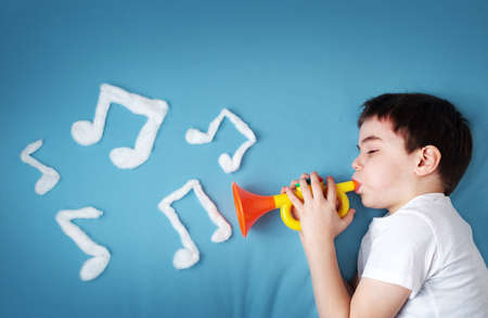 seven years: happy seven years old boy on blue blanket background with pipe and musical notes on blue background