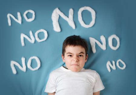 青い毛布の背景に不良少年。周りの言葉がないと怒っている子供 写真素材