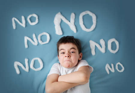 bad boy on blue blanket background. Angry child with no words around
