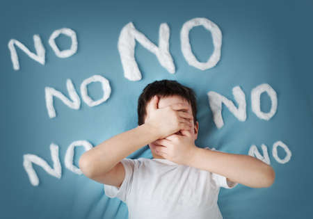 bad behavior: unhappy boy on blue blanket background. Angry child with no words around