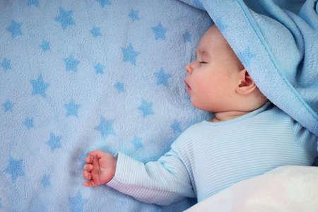 3 maanden oude baby slapen op blauwe deken met sterren