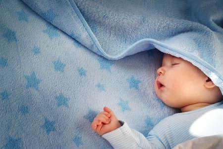 niño durmiendo: 3 meses de edad bebé durmiendo en una manta azul con estrellas