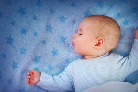 3 month old baby sleeping on blue blanket with stars