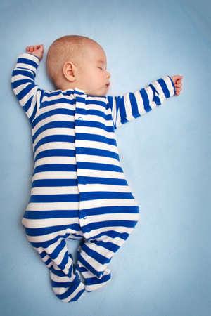 little boy sleeping on soft blue blanket