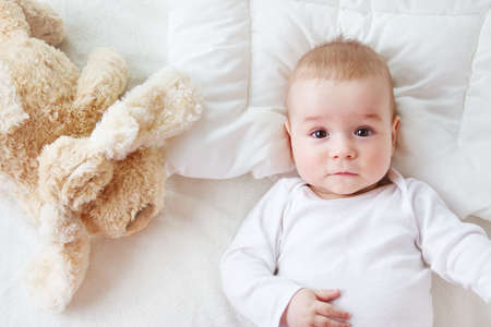 blanket: seven month old boy lying in the bed with a plush dog toy Stock Photo