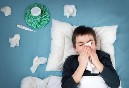Kranker Junge im Bett liegen. trauriges Kind mit Fieber und Eisbeutel auf dem Kopf