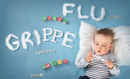 Ill boy lying in bed. baby with grippe text