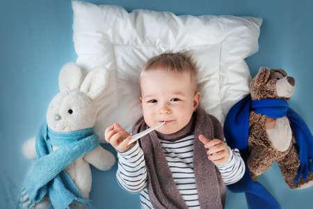病気の少年がベッドに横たわっています。発熱と頭の上の氷バッグ悲しい子 写真素材 - 53077191