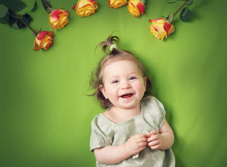 babygirl: pretty one year old babygirl lying on green blanket with yellow roses