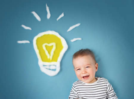 One year old boy with a bulb on blue background. Child with an idea Stock Photo