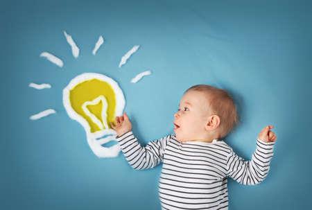 Een jaar oude jongen met een lamp op een blauwe achtergrond. Kind met een idee