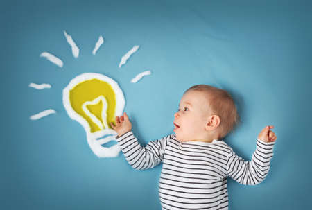 One year old boy with a bulb on blue background. Child with an idea Banque d'images