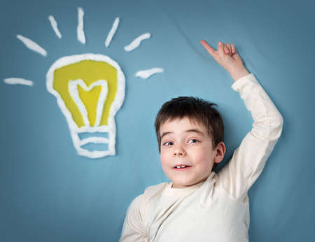 innovation concept: seven years old boy with a bulb on blue background. Child with an idea