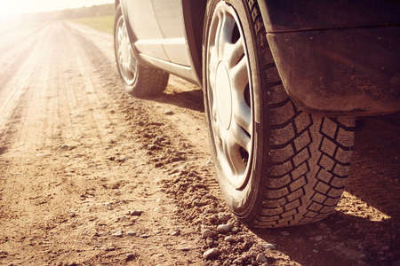 car wheel: car tire on gravel road in evening light Stock Photo