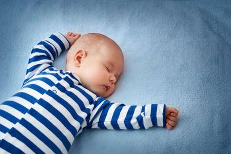 bebes: El pequeño dormir niño en una manta azul suave Foto de archivo