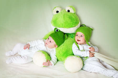 six months: two cute six month old babies lying in frog hats with a soft toy Stock Photo