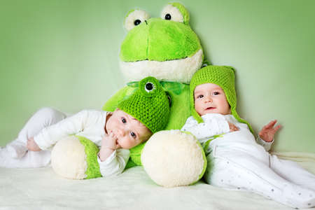 six month old: two cute six month old babies lying in frog hats with a soft toy Stock Photo