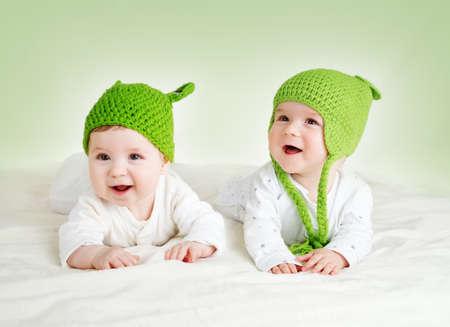 twee schattige zes maanden oude baby liggend in kikker hoeden op zachte deken