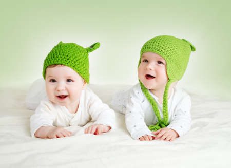 two cute six month old babies lying in frog hats on soft blanket