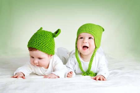 baby boys: two cute six month old babies lying in frog hats on soft blanket
