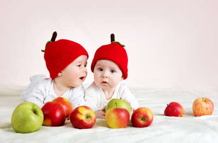 six month old: two cute six month old babies lying in hats on soft blanket with apples