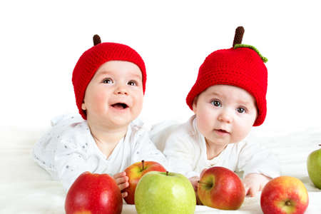 two cute six month old babies lying in hats on soft blanket with apples