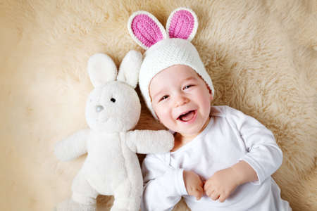 sleepy one year old baby lying in bunny hat on lamb wool background
