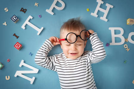 speak: One year old child lying with spectacles and letters on blue background