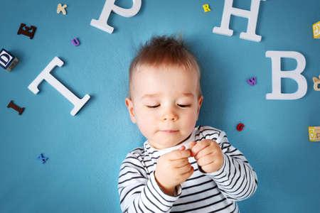 Ein Jahr altes Kind mit Brille und Buchstaben auf blauem Hintergrund liegen
