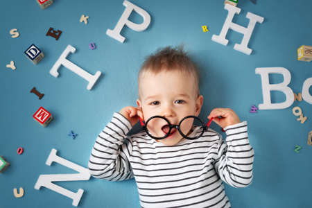 1 year old: One year old child lying with spectacles and letters on blue background
