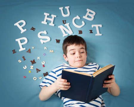zeven jaar oud kind liggend met boek en letters op een blauwe achtergrond