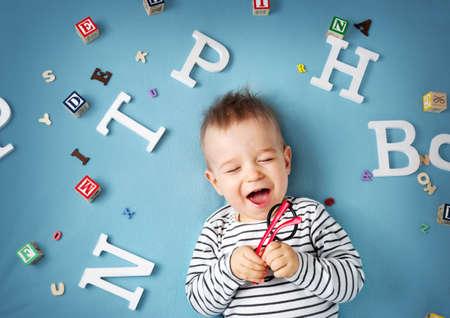 Un año de edad niño acostado con las gafas y letras sobre fondo azul Foto de archivo - 56033302