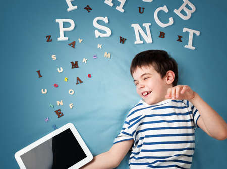 seven years: seven years old child lying with tablet and letters on blue background