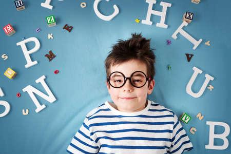 7 Jahre altes Kind mit Brille und Buchstaben auf blauem Hintergrund liegen