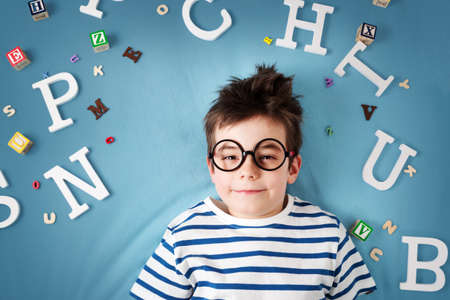 seven years old child lying with glasses and letters on blue background Archivio Fotografico