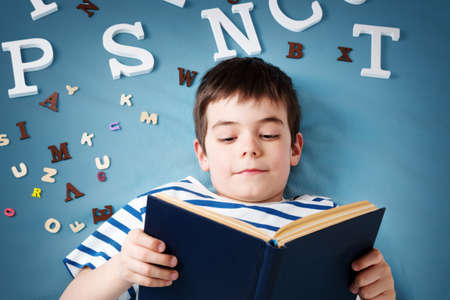 kid book: seven years old child lying with book and letters on blue background