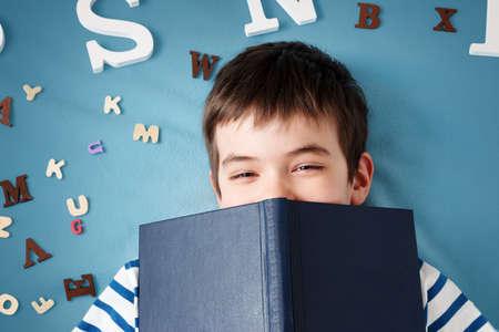 siedem lat dziecko leży z książką i litery na niebieskim tle