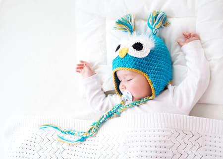 zeven maanden oude jongen slaapt in het bed in de hoed van de uil