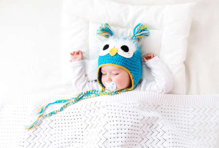 seven month old boy sleeping in the bed in owl hat Reklamní fotografie - 56033358