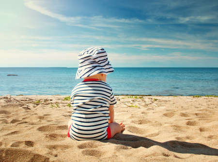 Nine month old baby boy sitting on the beach in beautiful summer day