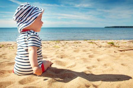 Neun Monate altes Baby, das auf dem Strand in schönen Sommertag sitzt