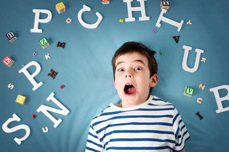 青色の背景の文字と横になっている 7 歳児 写真素材