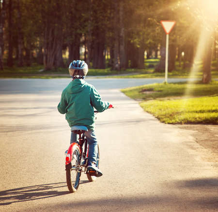 give way: child on a bicycle at asphalt road