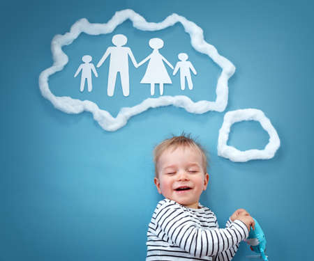 closed society: Little baby boy dreaming of a family on blue background