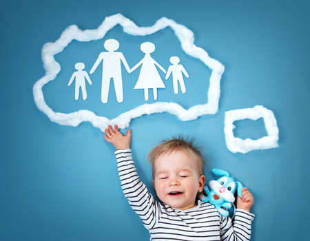closed community: Little baby boy dreaming of a family on blue background