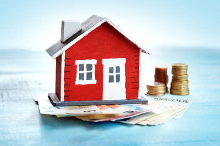 Red house model on wooden background with banknotes and coins Archivio Fotografico